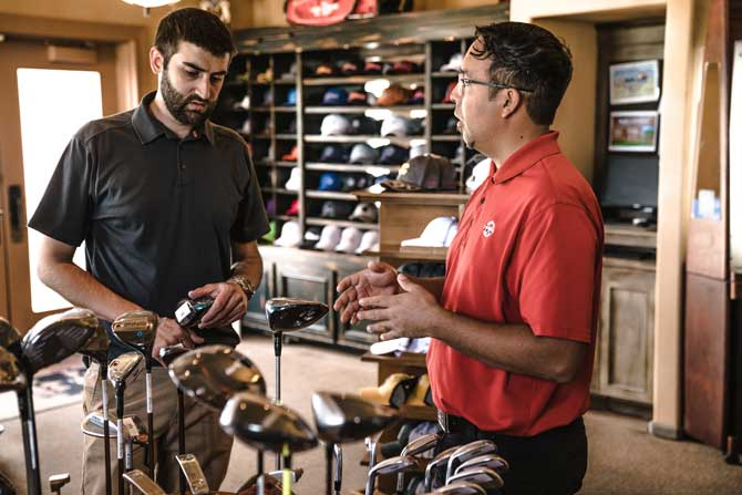 small business owner selling golf clubs to a young man